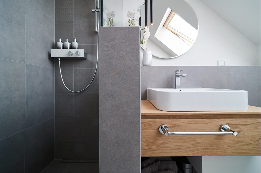 nes Tanke Bäderwerkstatt, Aqua Cultura Referenz, Dachbad, großformatige Fliesen, Waschtisch Holz, Holz im Bad, runder Spiegel, Raumtrenner