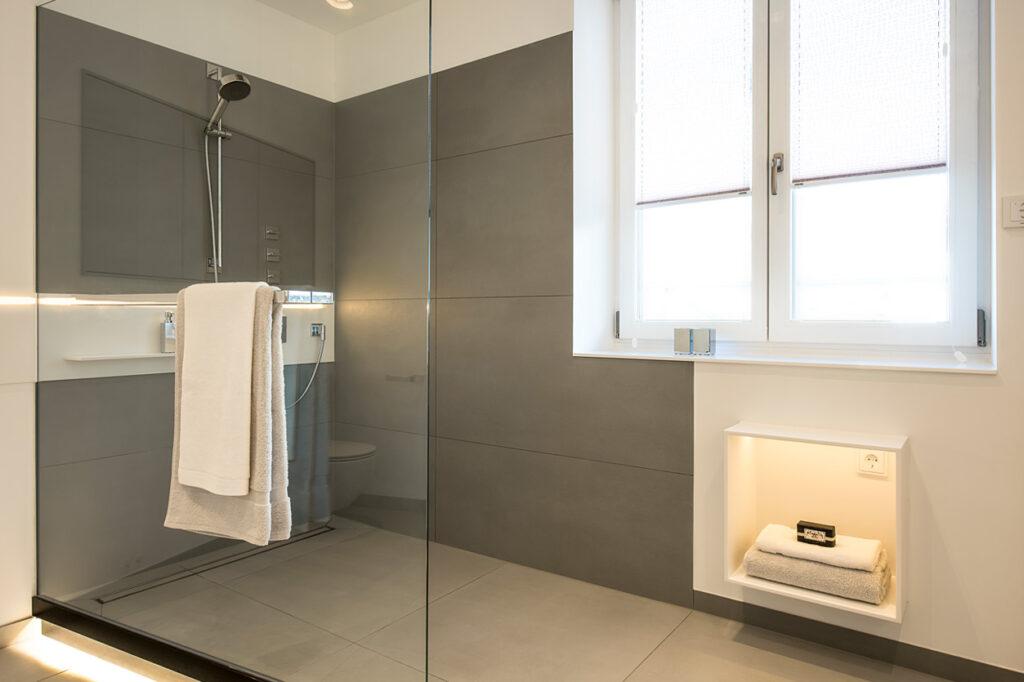 Bukoll Bad, Aqua Cultura Referenz, grosses Bad, Bad mit Fenster, Duschbereich, große Fliesen, anthrazit